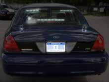 Short police radio antenna on trunk - Rear-facing radar - Light flashers in rear window - Government license plate - Police Interceptor badge
